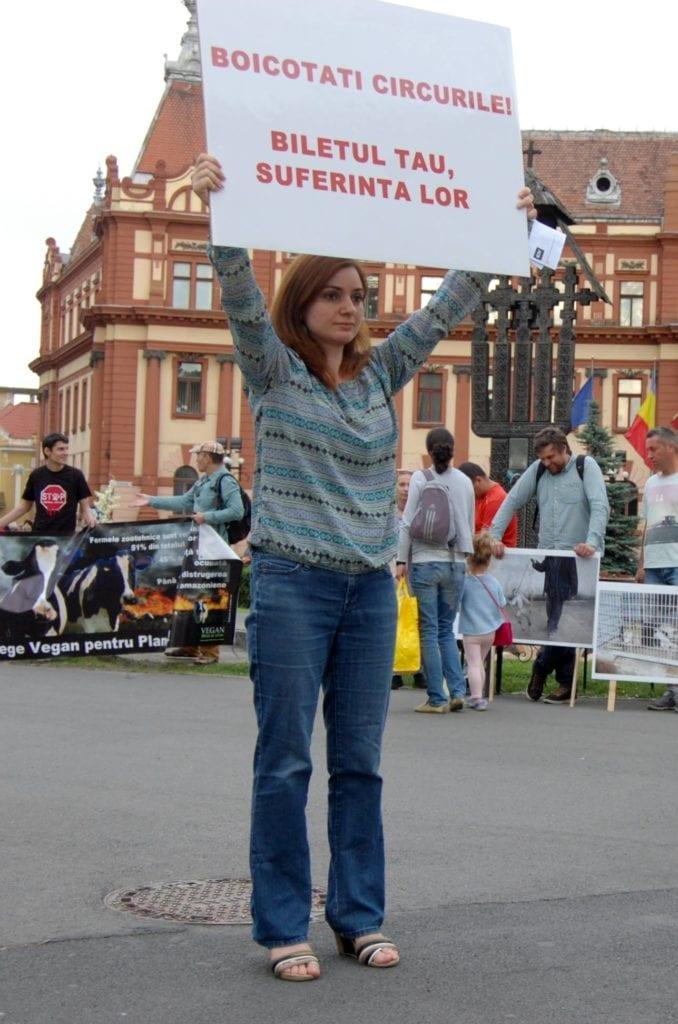 Activistă ținând un baner cu mesaj împotriva exploatării animalelor la circuri