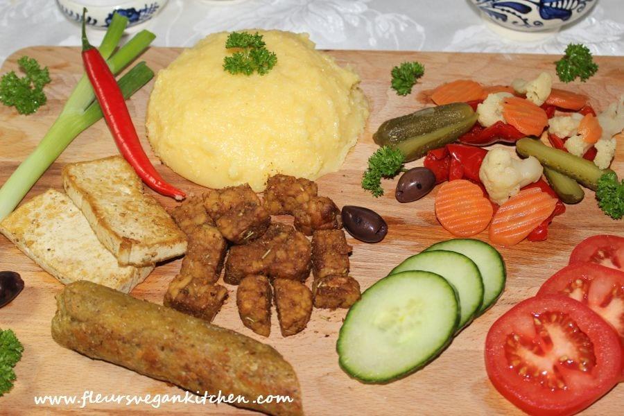 Platou cald de aperitive cu tofu, tempeh, seitan, mămăliguță, murături și legume. Sursa foto: Fleurs Vegan Kitchen