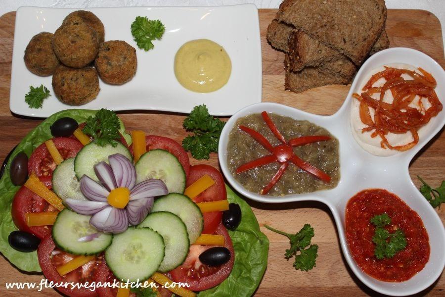 Platou rece de aperitive cu fasole bătută, salată de vinete, zacuscă, chifteluțe din năut și crudități: salată, roșii, castravete, ceapă rosie, măsline. Sursa foto: Fleurs Vegan Kitchen